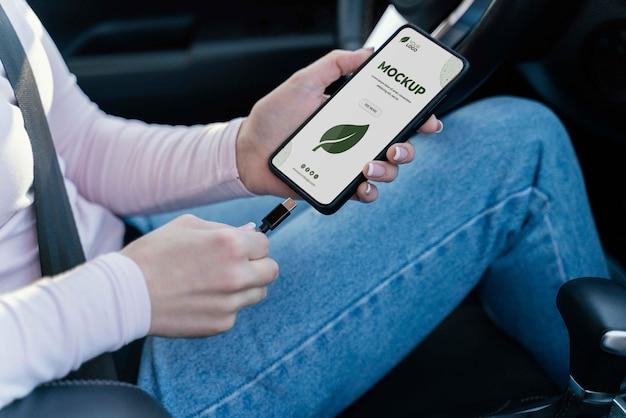 그녀의 모형 스마트폰을 충전하는 차에 있는 여자