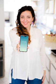 スマートフォンのモックアップを提示するキッチンの女性