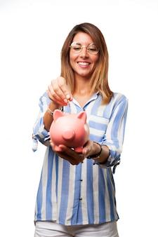돼지 저금통에 동전을 삽입하는 여자