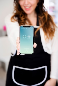 Woman in kitchen presenting smartphone mockup