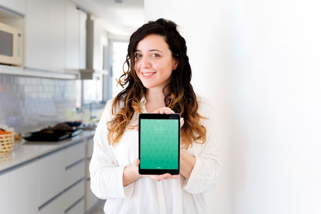 Woman in kitchen presenting tablet mockup