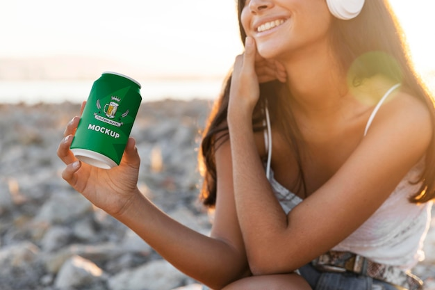 Woman listening to music on headphones with can of soda