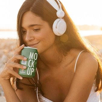 Женщина слушает музыку в наушниках, имея банку газировки