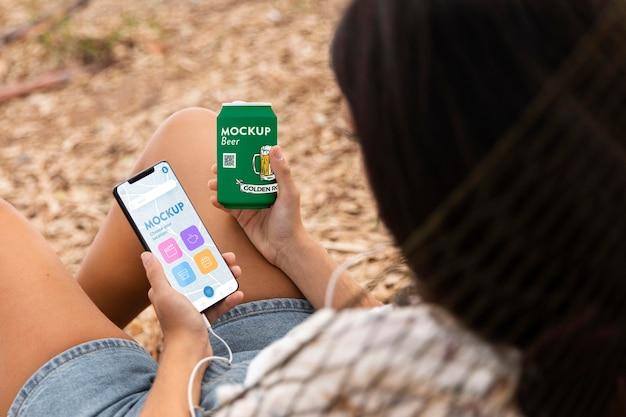 Женщина слушает музыку в наушниках со смартфоном и банкой содовой