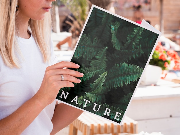 Woman looking into a nature book mock up