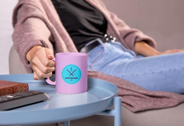 ピンクのマグカップとソファの上の女性