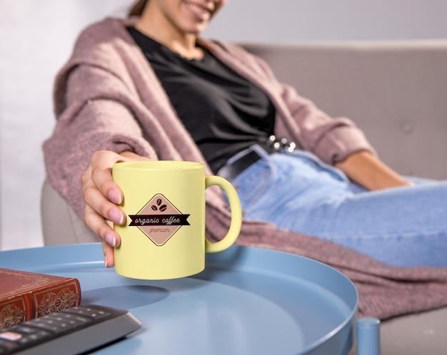 黄色のマグカップとソファの上の女性