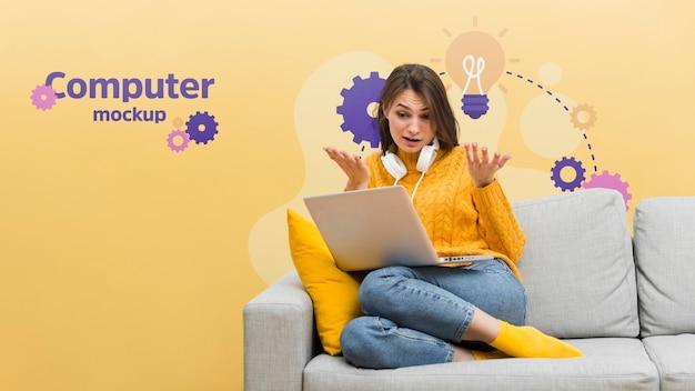 Женщина на диване работает на ноутбуке