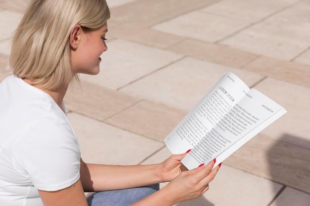 Женщина на улице, читая книгу
