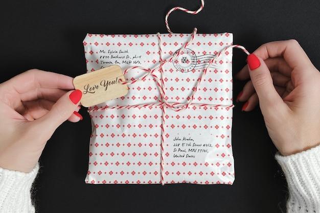Женщина открывает макет обернутой посылки