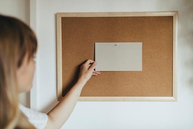 Woman pinning a picture mockup on a corkboard during coronavirus quarantine