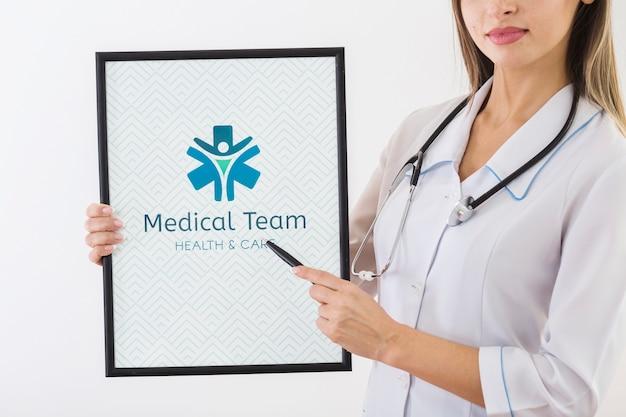 医療クリップボードを指している女性