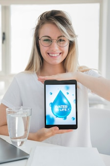 Woman presenting tablet mockup with water concept