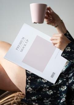 一杯のコーヒーで雑誌のモックアップを読んでいる女性