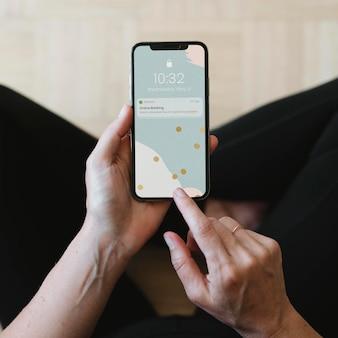 携帯電話のモックアップで銀行からのメッセージを読んでいる女性