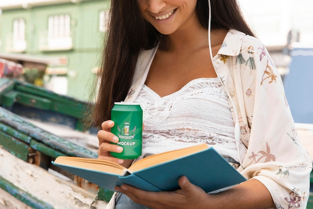 Woman reading book and drinking soda while listening to music
