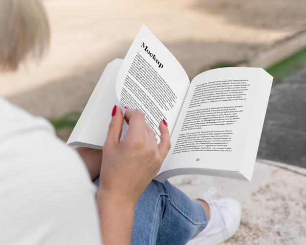 Woman reading book on street close up