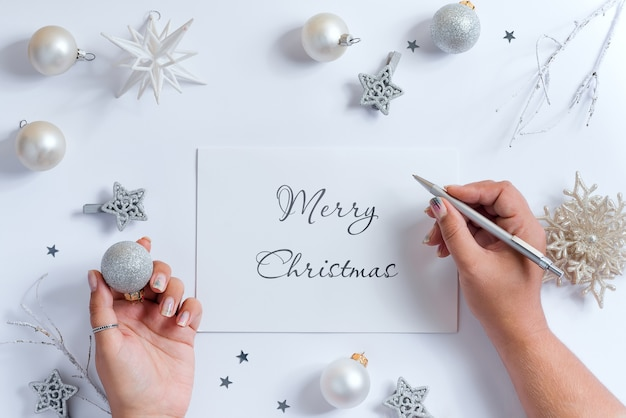 Woman's hands write letter mockup to santa above decoration.