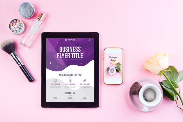 Woman's workplace with coffee, tablet phone and roses with cosmetics. top view
