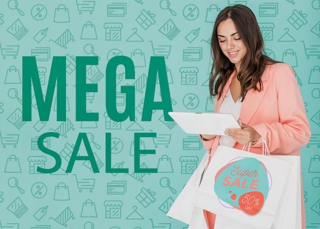 Женщина делает покупки на мега-продажах