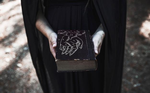 呪文で閉じた本を示す女性
