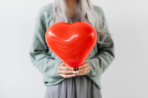 Женщина показывает макет красного шара в форме сердца