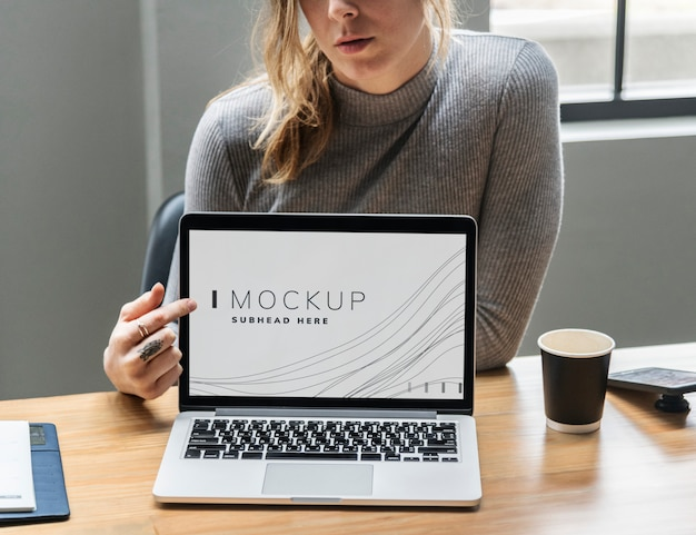 Woman showing a laptop screen mockup