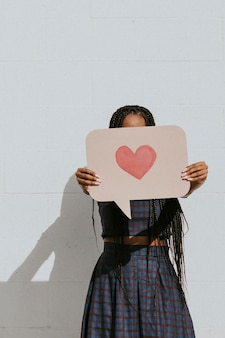Woman showing a speech bubble with a pink heart icon