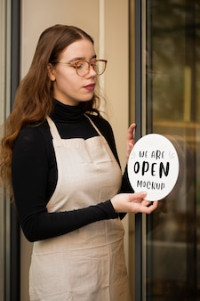 Woman showing a we are open mock-up sign