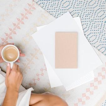 彼女の手で一杯のコーヒーとカーペットの上に座っている女性