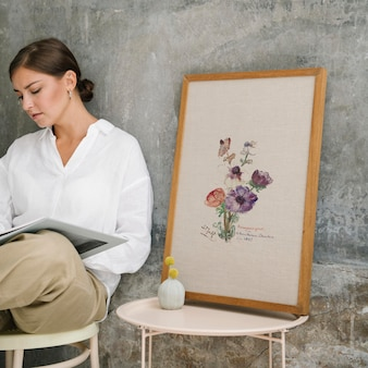 Woman sitting on a stool and reading a book by a photo frame