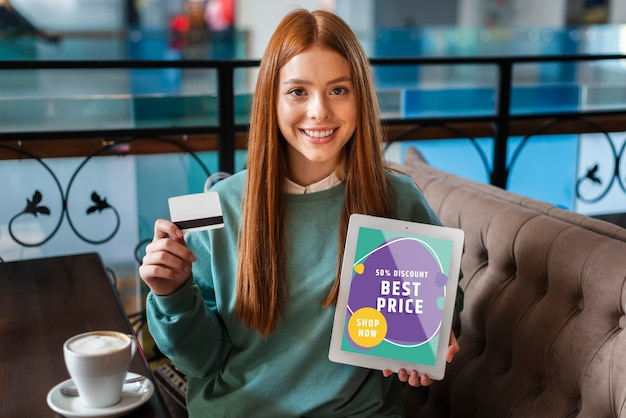 Woman smiling with a credit card and a tablet in her hands