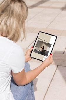 Woman on street reading book on tablet