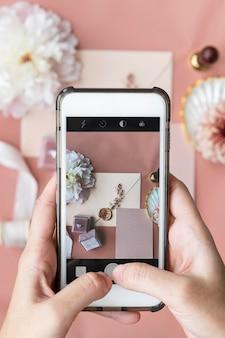 結婚指輪と招待状の写真を撮る女性