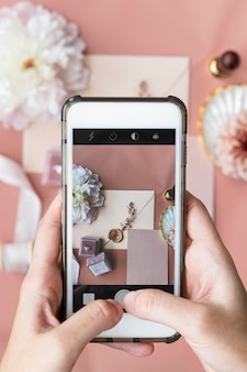Woman taking a photo of a wedding ring and an invitation