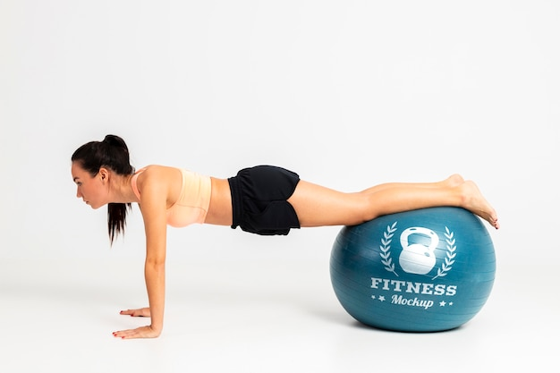 Woman training with fitness ball mock-up