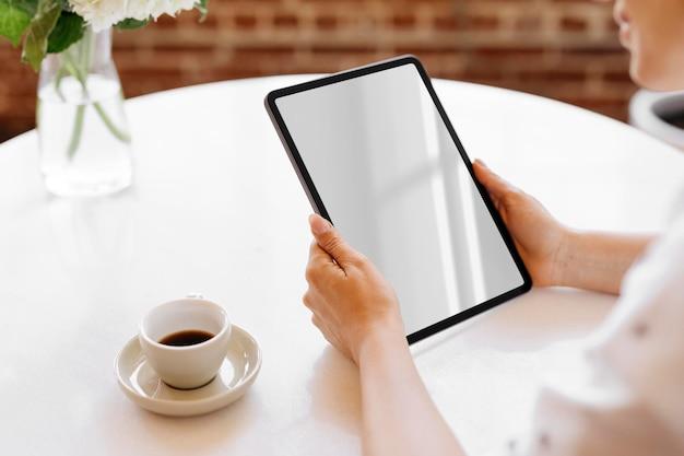 카페 모형에서 디지털 태블릿을 사용하는 여성