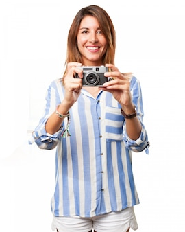 Woman using her old camera with a big smile