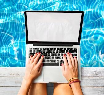 Woman using laptop at swimming pool