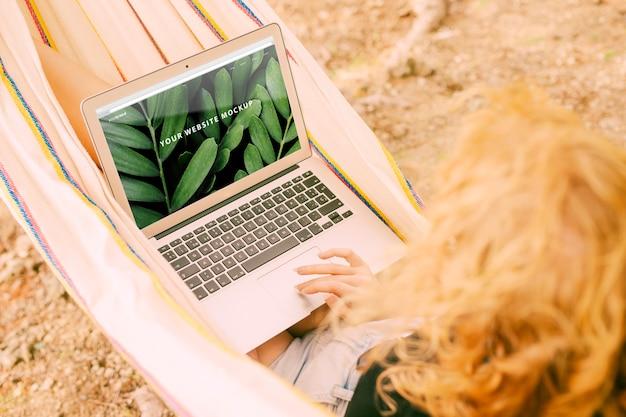 Женщина, используя ноутбук макет в природе