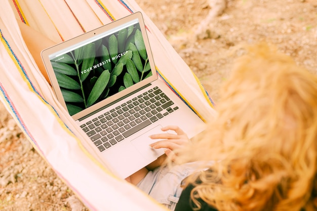 Woman using laptop mockup in nature