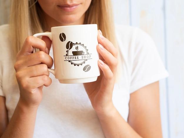 Женщина хочет пить из кружки кофе