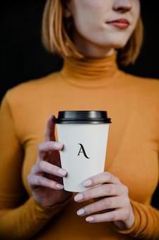 テイクアウトの紙コップのモックアップでタートルネックを着ている女性