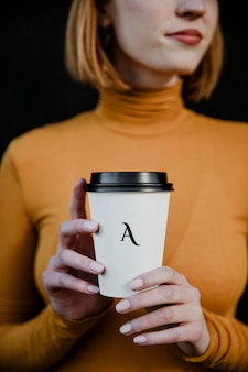 Woman wearing a turtleneck with a takeout paper cup mockup
