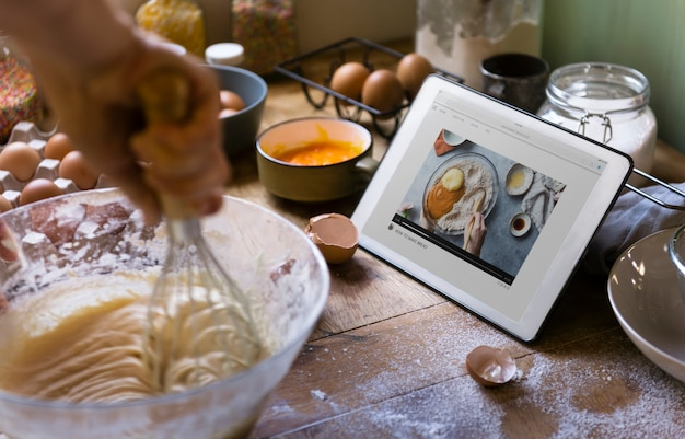 Woman whisking while looking at a recipe on a tablet