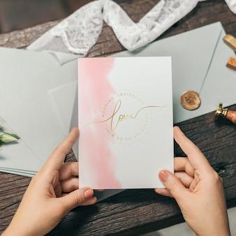 結婚式の招待カードのモックアップを持つ女性