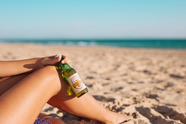 Donna con il modello di bottiglia di birra in spiaggia