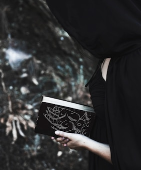 Woman with black hood reading from a spell book