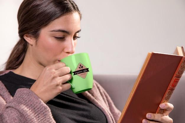 本と緑のマグカップを持つ女性