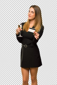 Woman with champagne celebrating new year 2019 holding a credit card